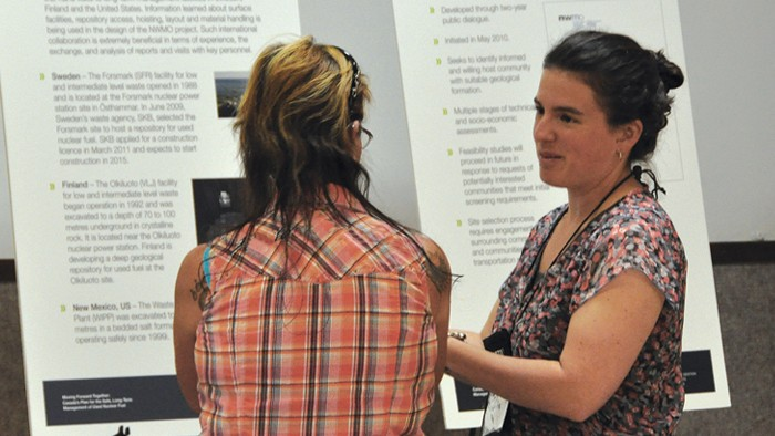 is photo shows a NWMO staff member in conversation with a community member at an open house event.