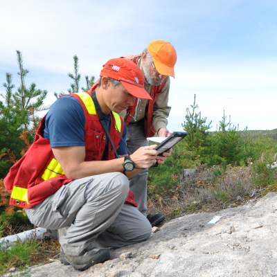 A photo of NWMO geologists outdoors examining rock and making notes