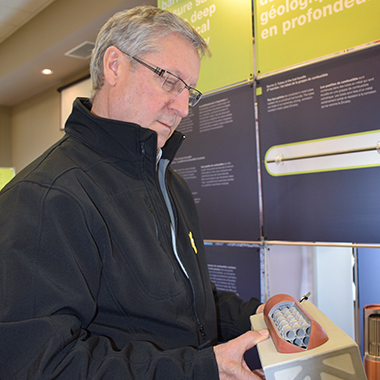 Larry McCabe, Chief Administrative Officer of the Town of Goderich, examines a model of a used fuel container.