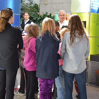This image shows an NWMO employee speaking with students at the Elliot Lake open house in April.
