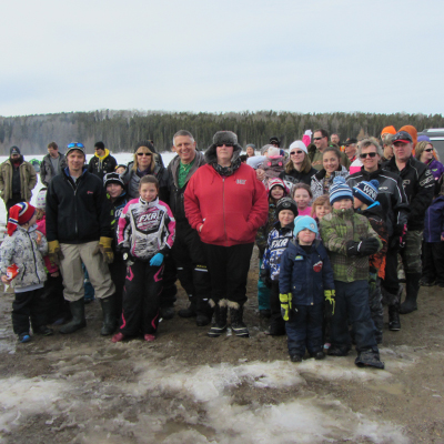This photo depicts a large group of men, women and children who participated in the Family Ice Fishing Derby held in Hornepayne. They gathered together for a group photo on the ice with the lake behind them.
