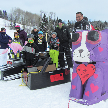 This is a picture of a group of local families seen with their cardboard box racers at the Kiwissa Ski Hill.