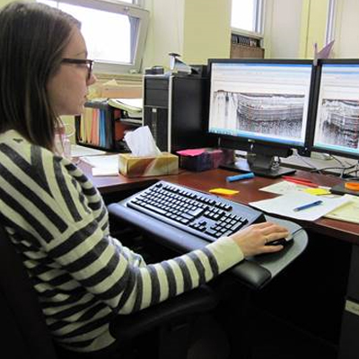GSC co-op student Fiona Davidson uses geophysical interpretative software to mark the top and bottom of submarine landslide deposits. The data is used to create maps showing the extent and thickness of the landslide deposits in the surveyed area