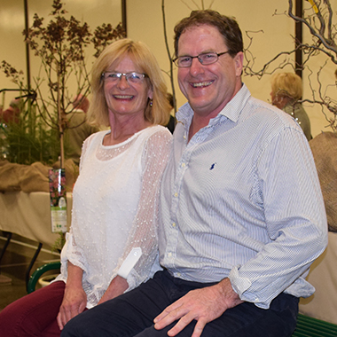 The photo shows NWMO Relationship Manager Paul Austin and wife Sue testing a garden bench they purchased at the dinner auction.