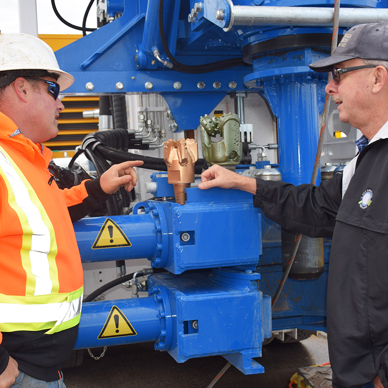 This picture shows a visitor looking at different drill bits in front of a drill rig during an open house held in Huron-Kinloss in November.