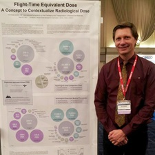 This picture depicts the NWMO's Ulf Stahmer in front of his award-winning poster that discusses his method of presenting radiological dose in terms of a flight-time equivalent dose.