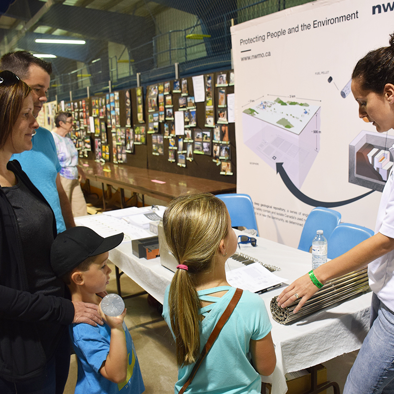 This photo depicts a family learning about used nuclear fuel from the NWMO's Cherie Leslie at the Teeswater Fair.