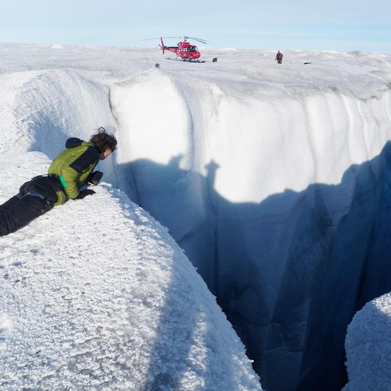 This image shows researchers and scientists observing features on the Greenland Ice Sheet to contribute to the Greenland Analogue Project with a helicopter in the background.