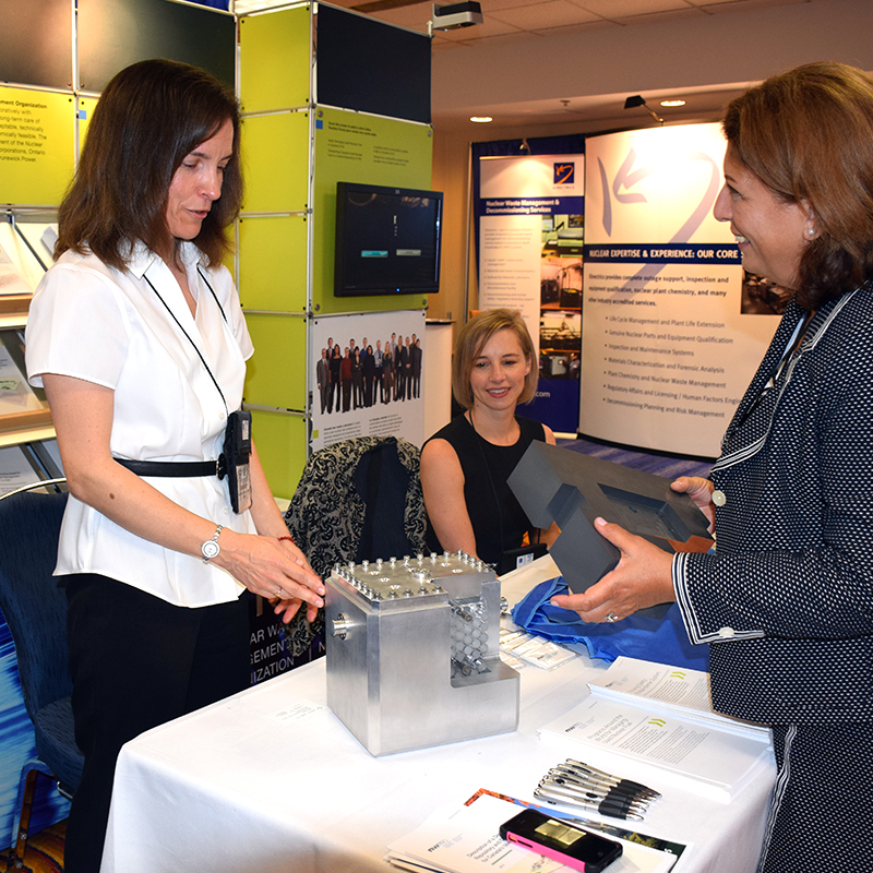An attendee visits the NWMO booth at the Canadian Nuclear Society Conference on Nuclear Waste Management, Decommissioning and Environmental Restoration.