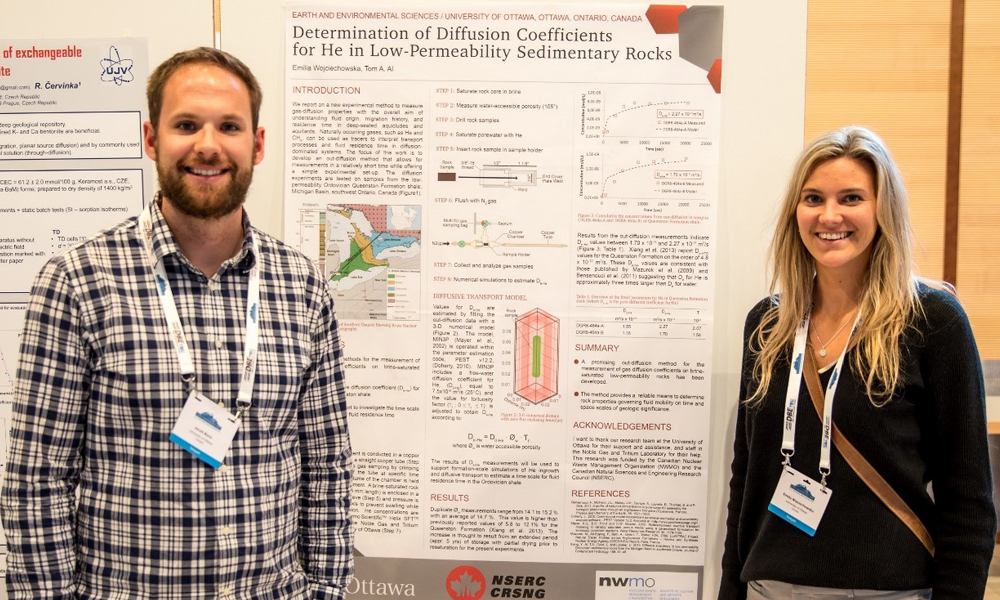 This image shows two students in front of their poster.