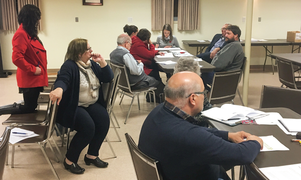 This photo shows members of  the South Bruce Council and Community Liaison Committee, and members of the public at two tables discussing and considering values and principles to guide more detailed  conversations around partnership.