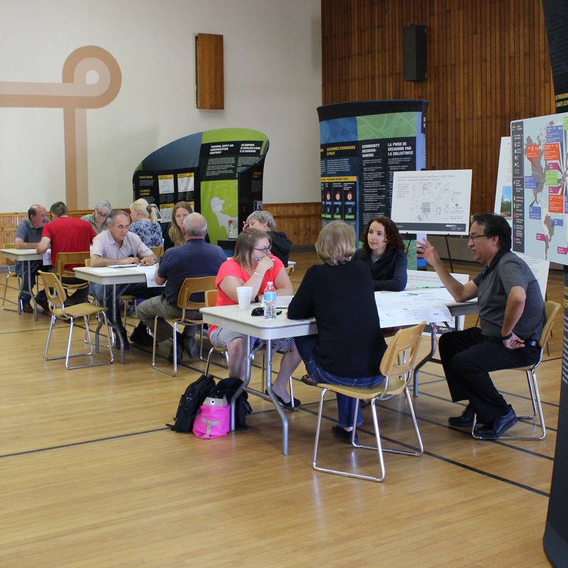 NWMO Staff and Manitouwadge residents study maps at open house.