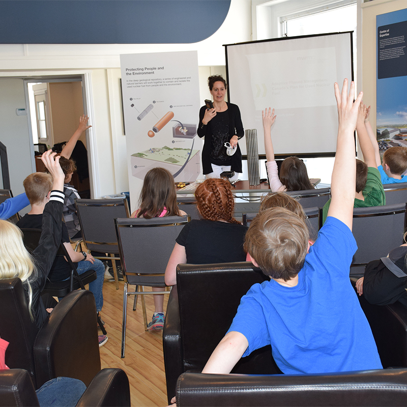 This picture depicts an NWMO employee engaging a Grade4/5 class of school children in an interactive presentation about radiation.