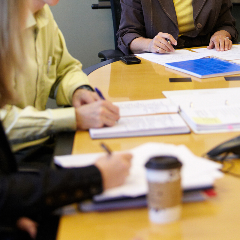Generic image of documents on a table with people around it