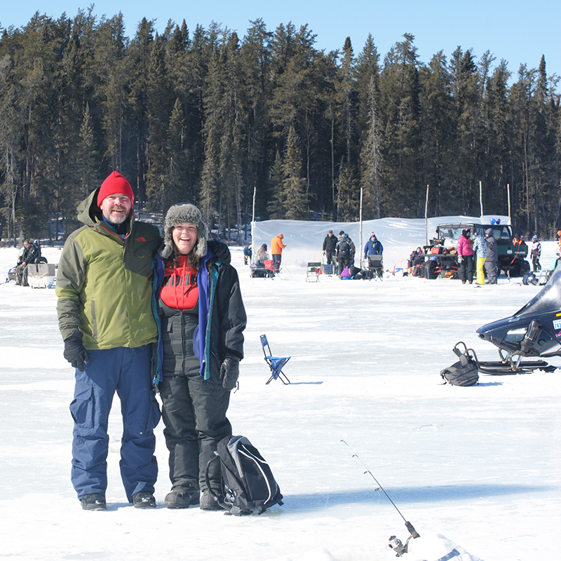 Two people stand on the snow, with winter activities in the background
