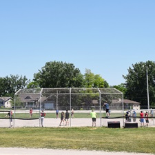 The photo shows a baseball diamond inside a large field, with children playing, and watching a ball game.
