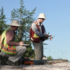 Two geologists studying areas of interest in Northern Ontario