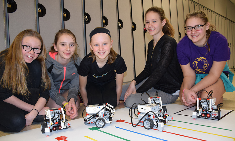 The photo is of five Grades 7 and 8 girls, side by side, on the floor with robots constructed out of LEGO kits by themselves and fellow classmates.