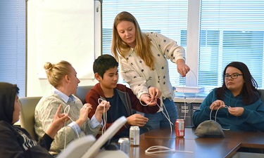 Senior Environment Scientist conducting an experiment with students