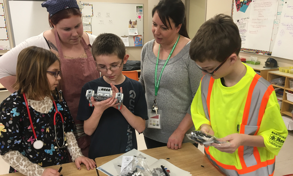 Three students work with robotics kits while two adults oversee the activities in a classroom