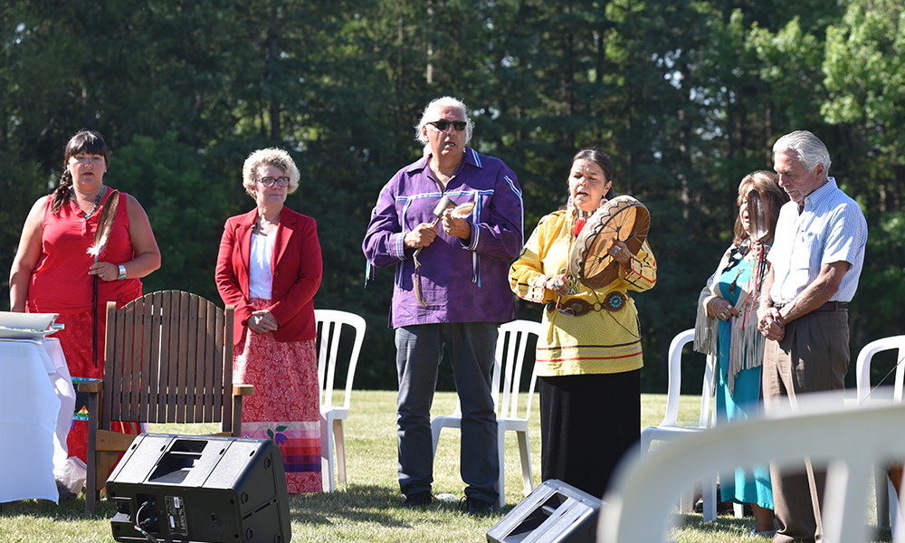 Image shows six people participating in an Indigenous drum ceremony.