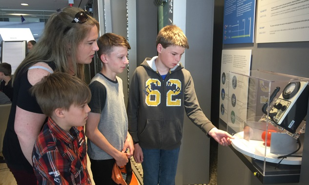 Image shows three young students with their teacher looking at an unspecified display item.