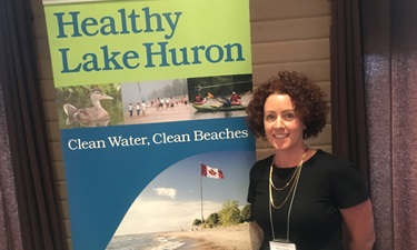 "A woman standing in front of a ""Healthy Lake Huron"" poster."