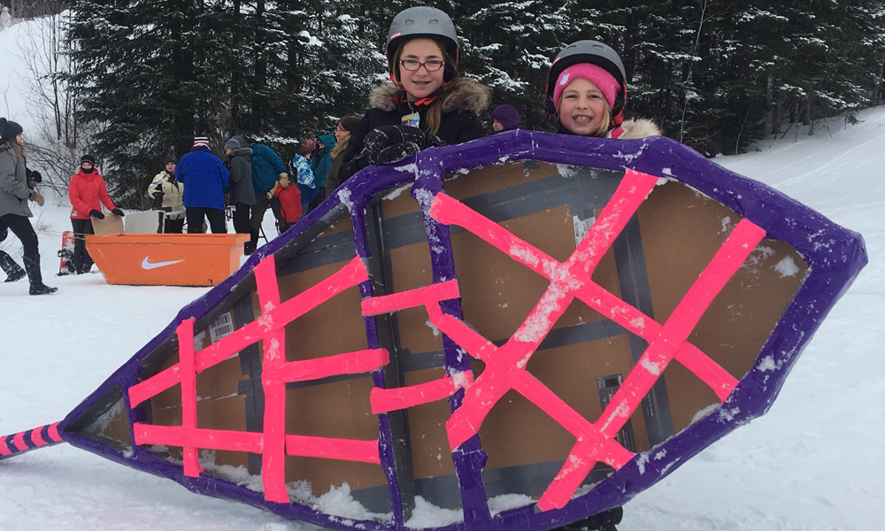 Photo depicts two young residents standing on snow with their colourful snowshoe-themed cardboard box racer.