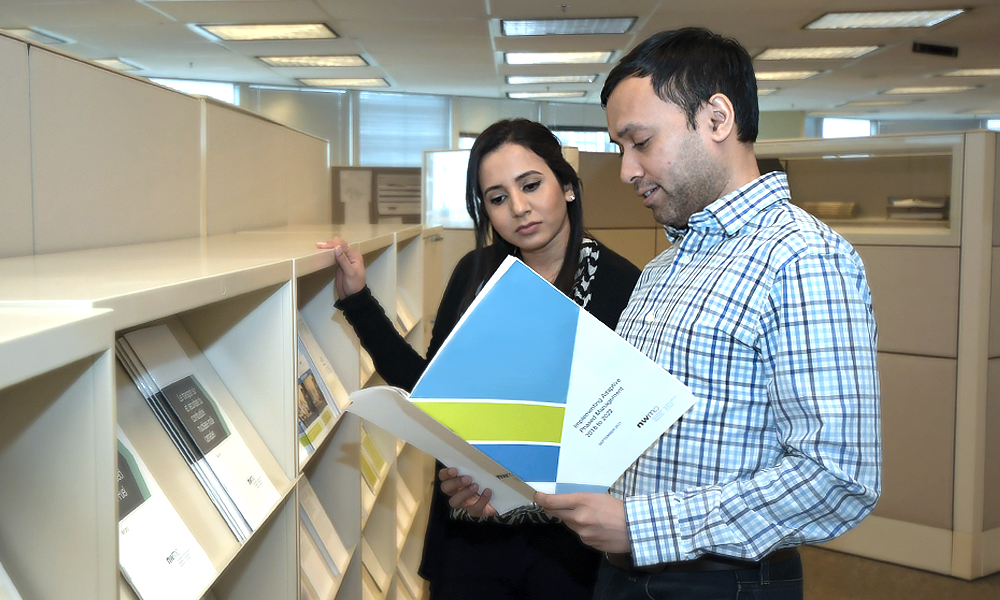 Image shows two people reading the implementation plan.