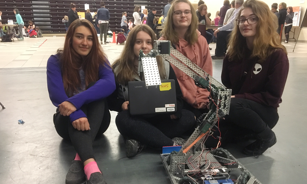 Image shows four girls sitting behind their robotic creation.