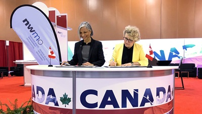 This is a photo of NWMO President and CEO Laurie Swami, together with Rumina Velshi, President and Chief Executive Officer of the Canadian Nuclear Safety Commission, signing a service agreement recommitting to a positive and constructive working relationship.